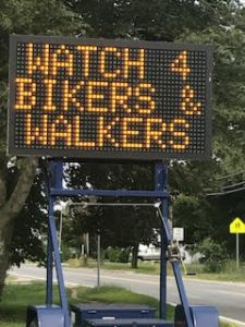 Biking on Cape Cod features a local sign reminds drivers to watch for bikers and walkers on Cape Cod